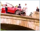 A scene from an an accident with a car and a damaged parapet.